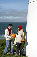 Young couple holding pumpkins at lighthouse.