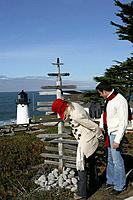 Young couple at lighthouse looking at directions post.