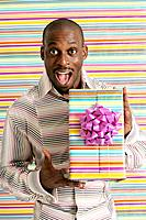 Excited African American man holding present