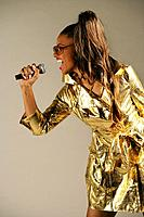 Young stylish African American woman singing in microphone, studio shot.