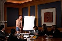 Man in underwear standing by flipchart in front of colleagues in conference room