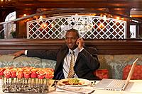 Business man using mobile phone at restaurant table, newspaper and laptop by plate