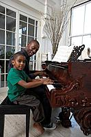 Father teaching piano to son 6_7, side view