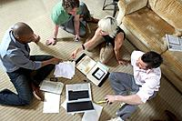 Three men and woman sitting on floor with laptop, discussing, elevated view