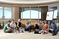 Group of people sitting in hotel room with laptop, portrait
