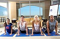 Four people practicing yoga in yoga class