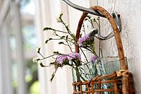 Vase of flowers in hanging basket on wall