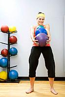 Mid adult woman holding three fitness balls in gym, smiling, portrait