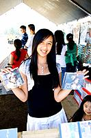 Hmong woman age 17 selling music cds in booth  Hmong Sports Festival McMurray Field St Paul Minnesota USA