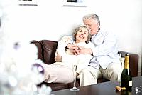 Senior couple lying on couch with champagne and Christmas tree in foreground