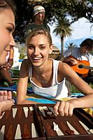 Young woman playing backgammon on beach, smiling, portrait