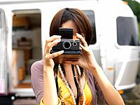 Young woman using instant camera