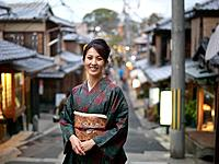Japan, Kyoto, woman in kimono standing in street, portrait