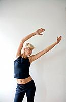 Young woman exercising against white wall