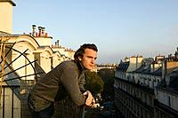 France, Paris, young man leaning on balcony at sunrise