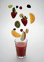 Fruit slices hovering over glass of fruit juice, studio shot
