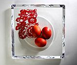 Colored eggs on glass plate