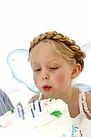 Girl 4_5 with fairy wings blowing out candle on birthday cake