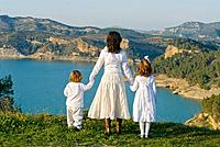 Spain, Malaga, mother and children looking at lake, rear view