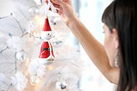 Woman putting ornament on Christmas tree, differential focus