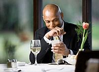 Business man using PDA at table in restaurant