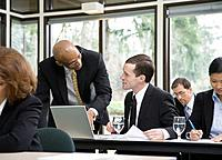 Two business men using laptop among colleagues in meeting