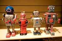 Four vintage toy robots on shelf