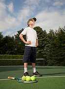 Boy 6_7 standing on tennis court next to racket and balls
