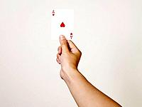 Young woman holding ace of hearts playing card, close_up of arm and hand, studio shot