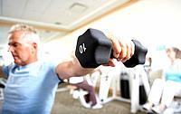 Man weight lifting in gym focus on hand in foreground
