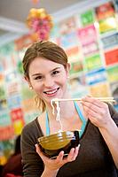 Young woman eating noodles with chopsticks, portrait