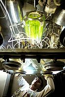 Glove box handling of radioactive waste. Nuclear technician using a glove boxe to handle low_level radioactive waste. The radioactive materials have b...