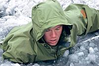 Military arctic survival training. Navy recruit in icy water, during arctic survival training in Northern Greenland. The recruit is training to become...