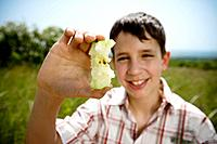 Boy holding up apple core (thumbnail)