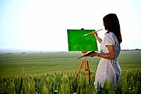 Woman painting in wheat_field, rear