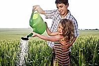 Boy helping girl with watering can (thumbnail)