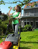 Woman mowing lawn in the sun