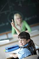 School girl raising hand in class