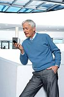 Man standing in office with phone