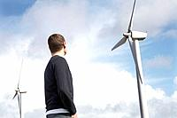 Man looking at wind turbines