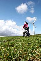 Woman riding a bike on a wind farm (thumbnail)