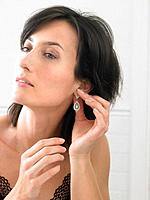 Woman putting on earrings