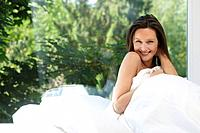 Woman in bed, smiling