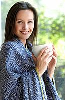 Woman with a cup, smiling at camera
