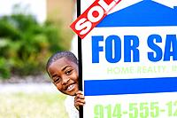 Little Boy Peeking Around Real Estate Sign