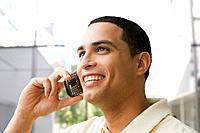 Hispanic man talking on cell phone outdoors