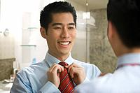 Korean businessman adjusting tie in mirror