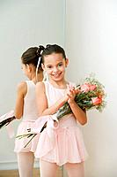 Hispanic girl ballerina holding bouquet