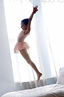 Hispanic girl in ballet costume jumping on bed