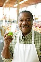 African grocer holding apple